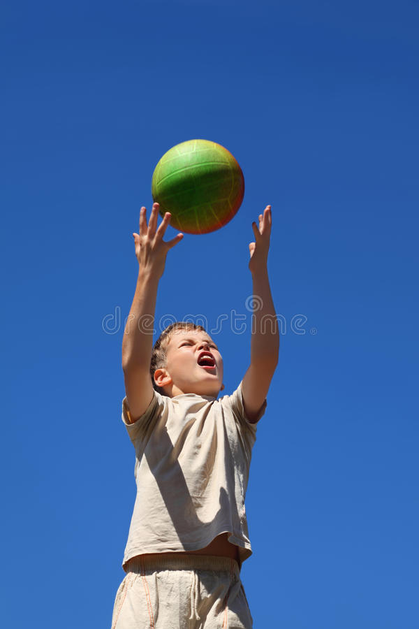 Boy carrom up ball upwards and yell royalty free stock images