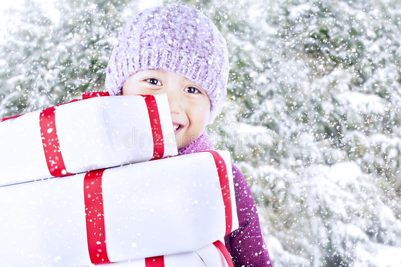 Boy carry christmas gifts on snow background. Boy bring christmas gifts with snow and pine tree background stock images