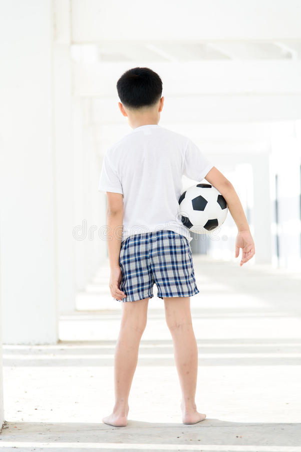 Boy carry football. Young Asian boy carry football in the empty white building royalty free stock image