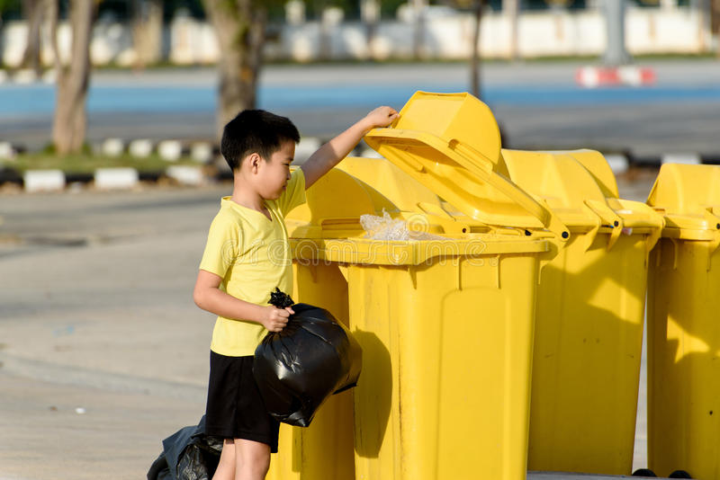 Boy carry garbage in bag for eliminate to the bin. Young Asian boy carry garbage in plastic bag for eliminate in the yellow bin under the sunlight stock photo