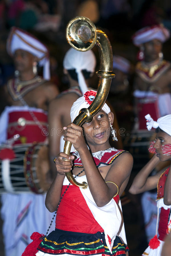 A boy carrying a ceremonial horn parades through the streets of Kandy during the Esala Perahera in Sri Lanka. stock photography