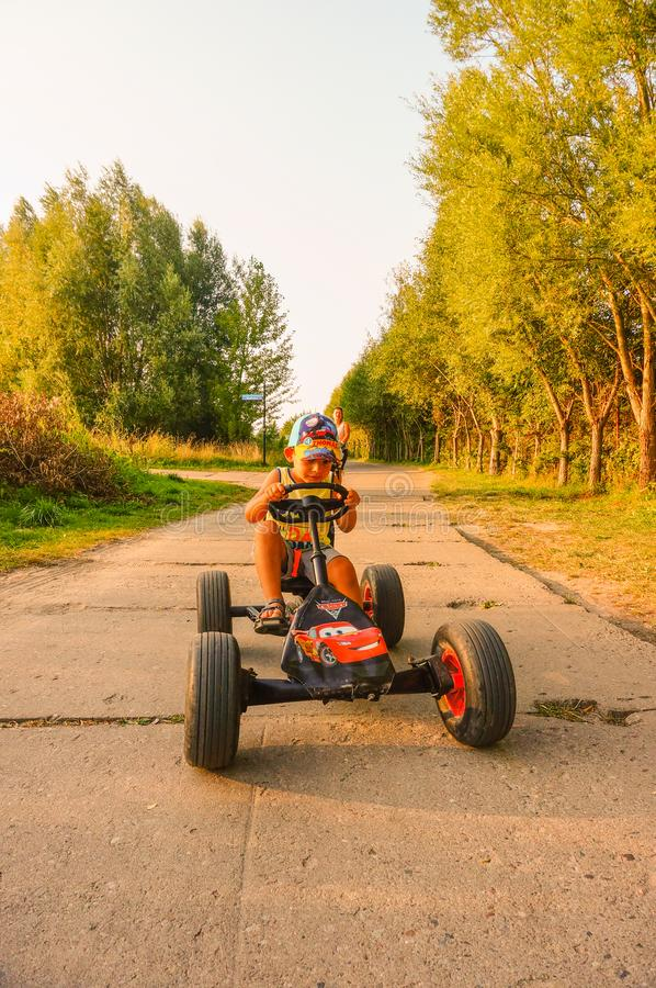 Boy on cart. Sarbinowo, Poland - August 9, 2018: Boy riding a pedal go kart on a road between grass and trees stock photography