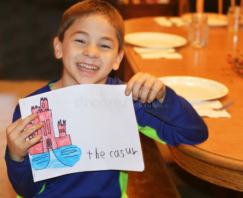 Boy Castle Art. A boy holding his picture that he drew of a castle, but he spelled castle wrong. He is very happy stock photo