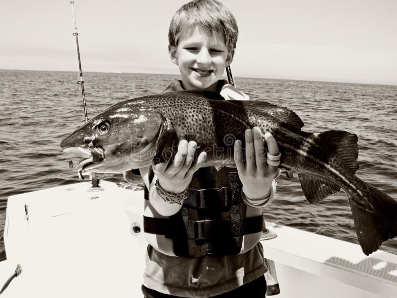 boy catches fish arkivfoton