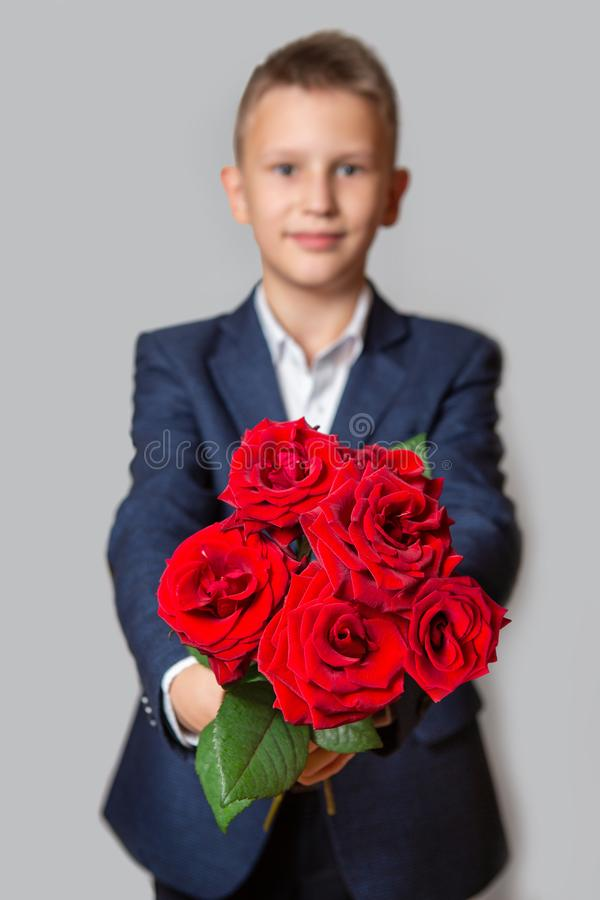 A boy in a blue suit holds a bouquet of red roses. Grey background. stock images