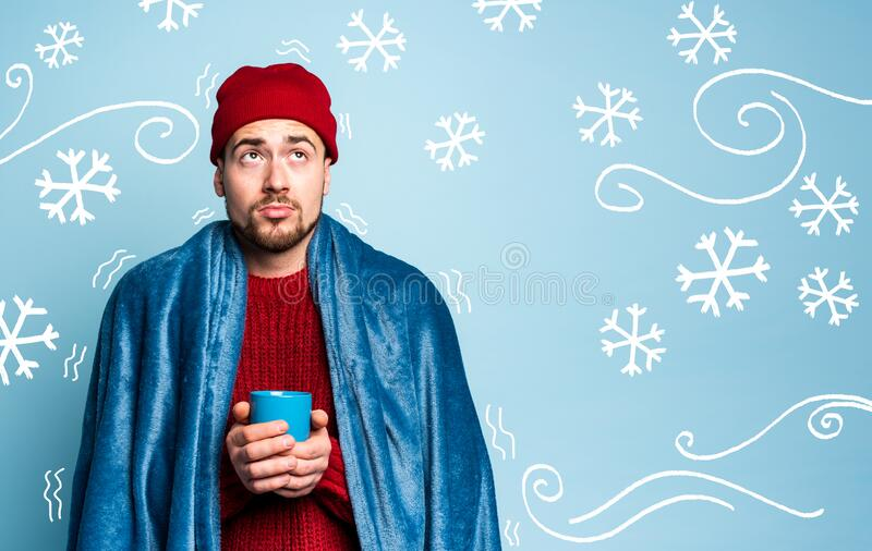 Boy caught a cold and drinks hot the. Cyan background. Concept of illness royalty free stock photography
