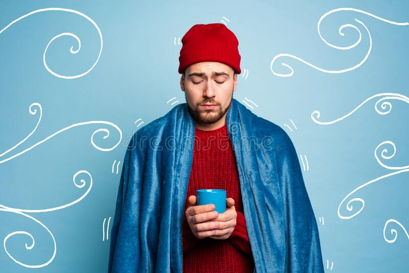 Boy caught a cold and drinks hot the. Cyan background. Concept of illness royalty free stock images