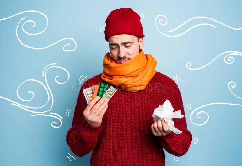 Boy caught a cold and uses pills to heal. Studio on Cyan background royalty free stock image