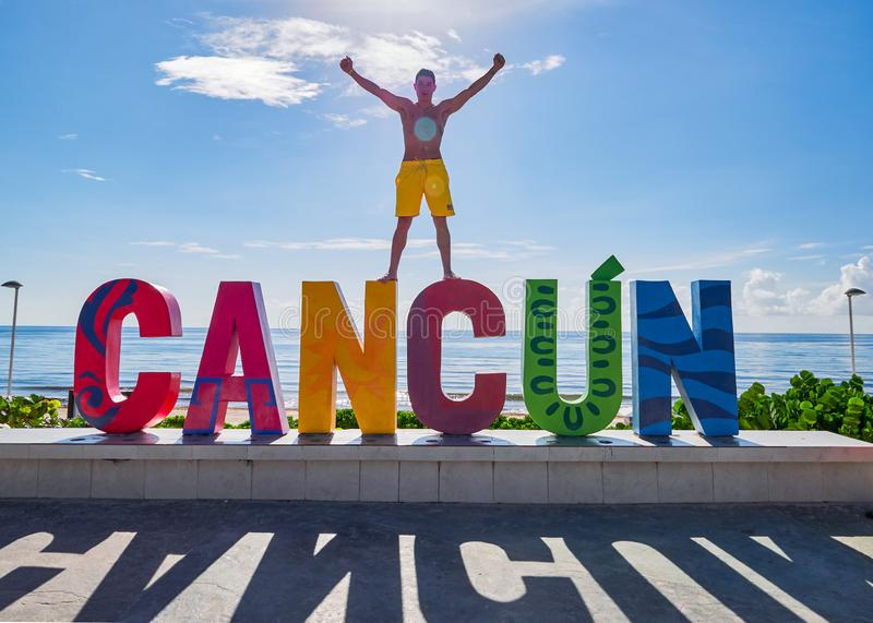 Boy raised arms on Cancun sign royalty free stock image