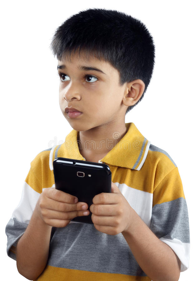 Boy With Cell phone. Indian Little boy Looking somewrehere with cell phone stock images