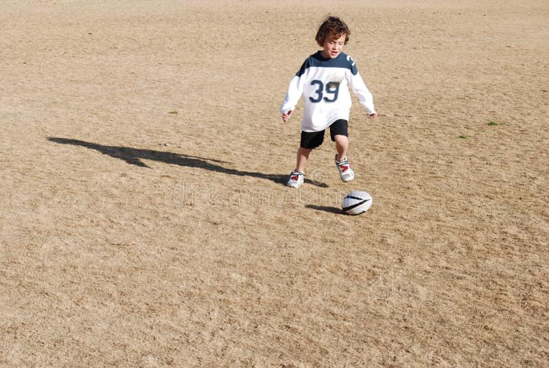 Boy chasing football stock photo