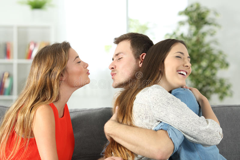 Boy cheating to his girlfriend with her best friend stock photos
