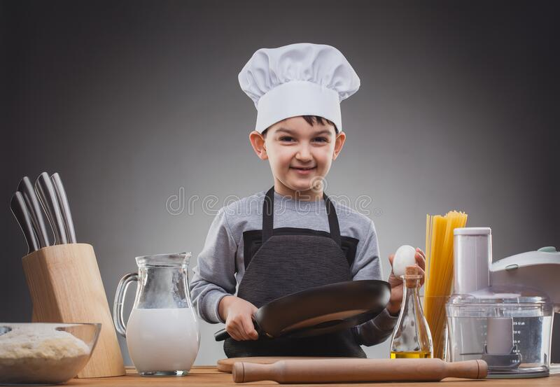 Boy Chef Cooking on a gray background. stock photos