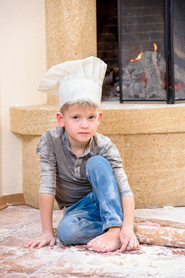 A boy in chef`s hats near the fireplace sitting on the kitchen floor soiled with flour, playing with food, making mess royalty free stock photos