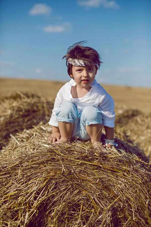 Boy child in bandana and white shirt sitting on a bale of hay royalty free stock image