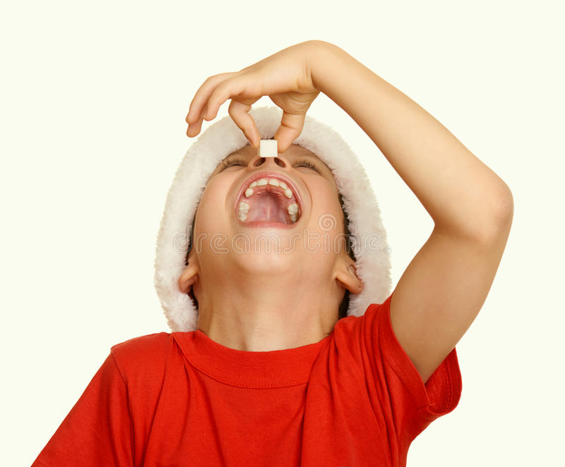 Boy child eat sugar in santa hat, having fun and emotions, winter holiday concept, yellow toned stock image