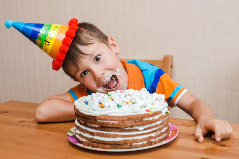 Boy the child is eating his birthday cake. The smeared face in a sweet cream royalty free stock image