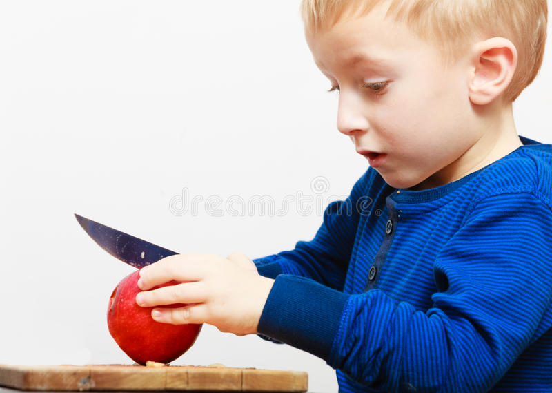 Boy child kid preschooler with knife cutting fruit apple at home stock photography