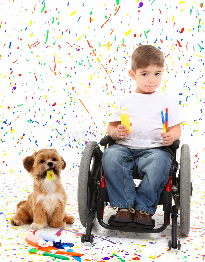 Boy Child Painting Wheelchair with Dog. Adorable 2 year old child with wheelchair painting with dog over paint splatter background royalty free stock images