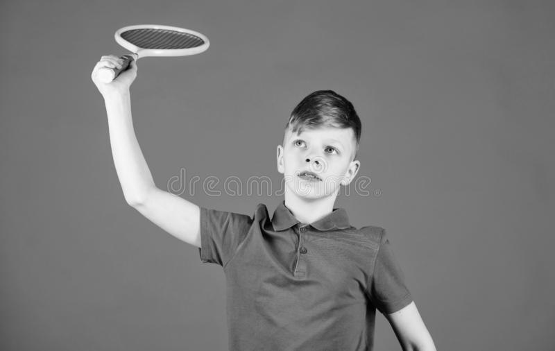Boy child play tennis. Practicing tennis skills. Guy with racket enjoy game. Future champion. Dreaming about sport. Career. Athlete kid tennis racket on blue royalty free stock photos