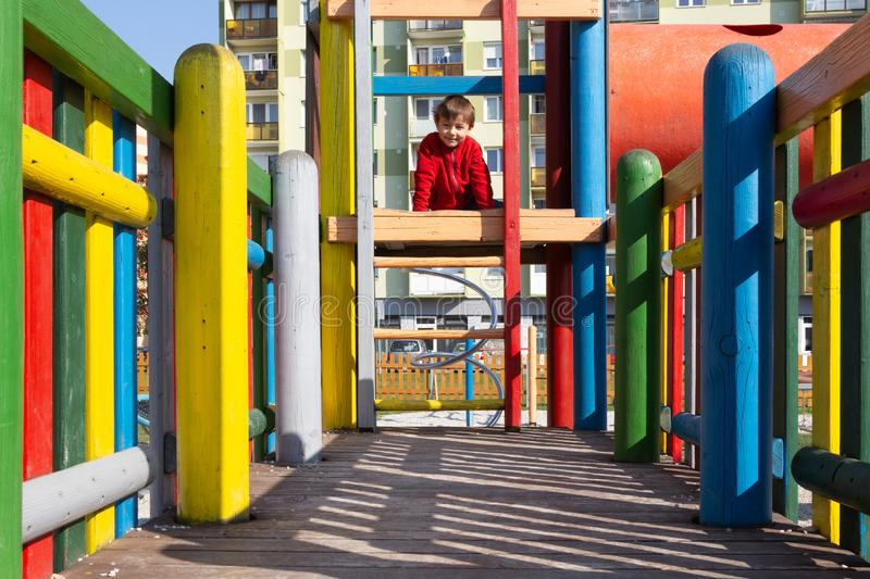 Boy child at playground. Sitting on a wooden toy castle royalty free stock photography