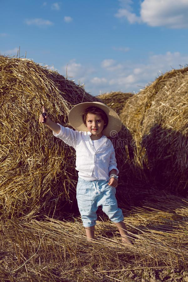 Boy a child in a straw hat and blue pants stands in a mowed field with stacks royalty free stock photo