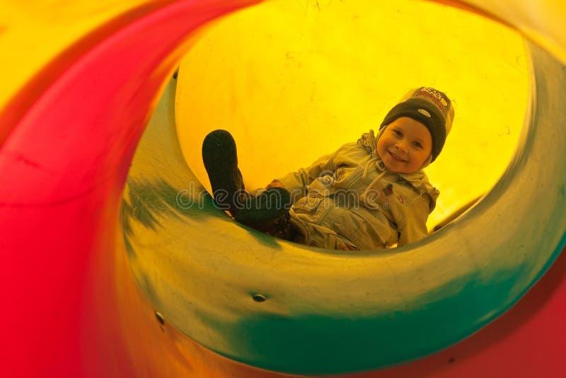 Boy child in tube slide stock photo