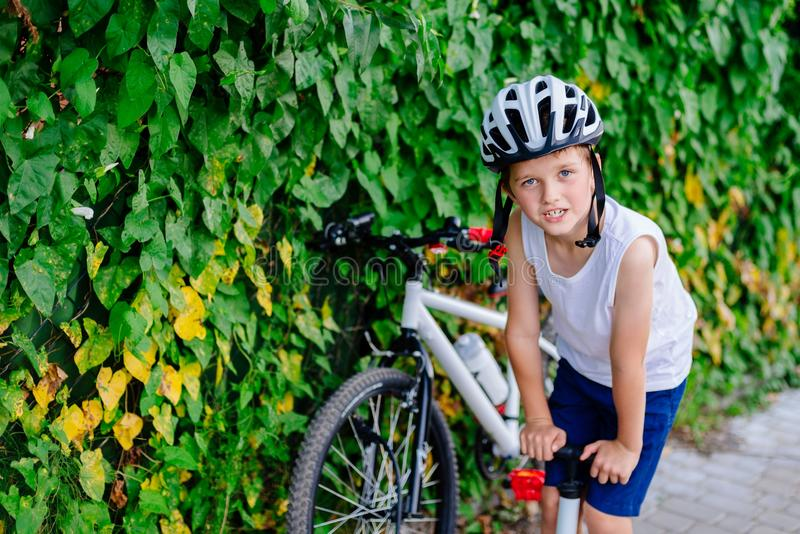 Boy child in white bicycle helmet inflating tire. With foot pump . Child on bike royalty free stock photos