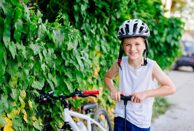 Boy child in white bicycle helmet inflating tire. With foot pump . Child on bike royalty free stock image