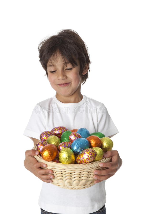 Boy with chocolate Easter eggs. Little boy with a basket of chocolate Easter eggs on white background royalty free stock photo