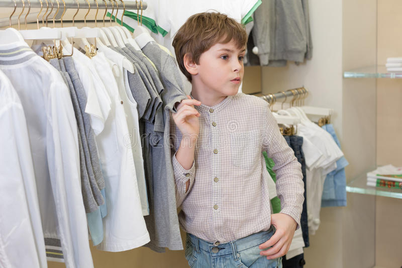 The boy chooses clothes in store stock photography