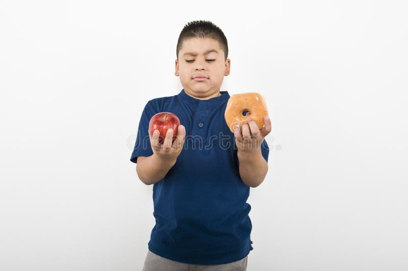 Boy Choosing Between Apple And Doughnut royalty free stock photography