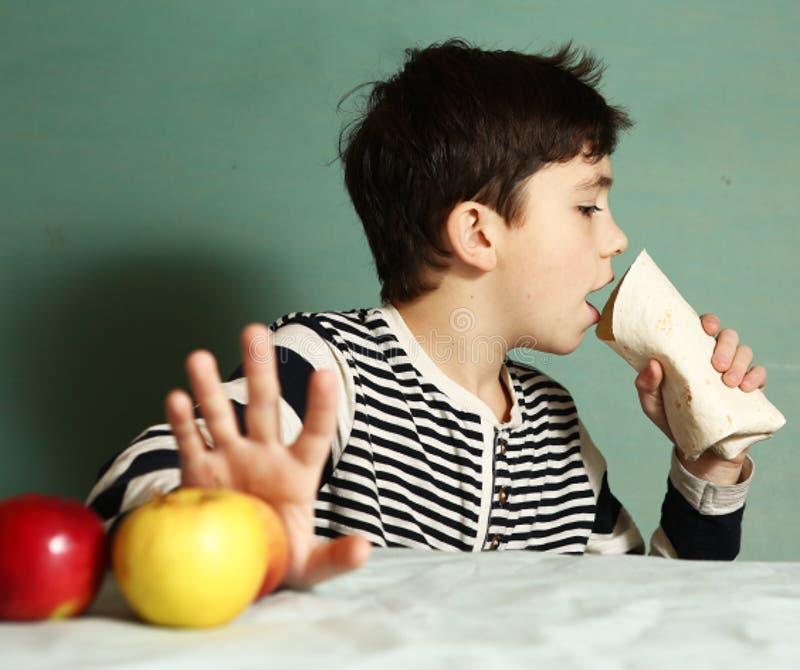 Boy choosing junk food roll refuse from apple. S. Choice between fast food versus healthy food diet stock images