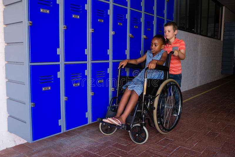 Boy with classmate sitting on wheelchair by lockers. In corridor at school royalty free stock photo