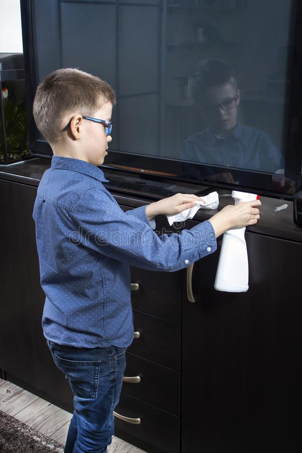 Boy cleaning the room. He applies detergent for furniture with an applicator. In the other hand, he holds a white wiping cloth. The boy cleaning the room. He royalty free stock images