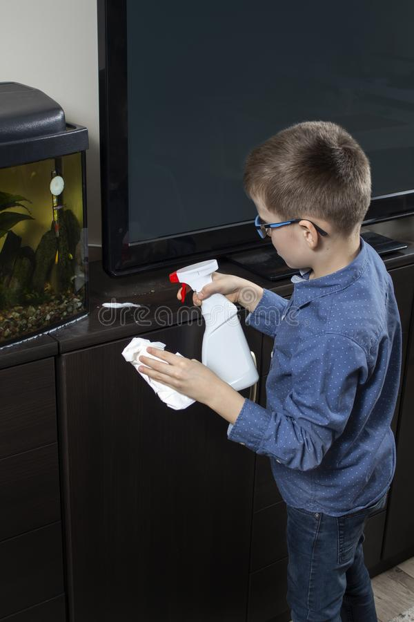 Boy cleaning the room. He applies detergent for furniture with an applicator. In the other hand, he holds a white wiping cloth. The boy cleaning the room. He stock images