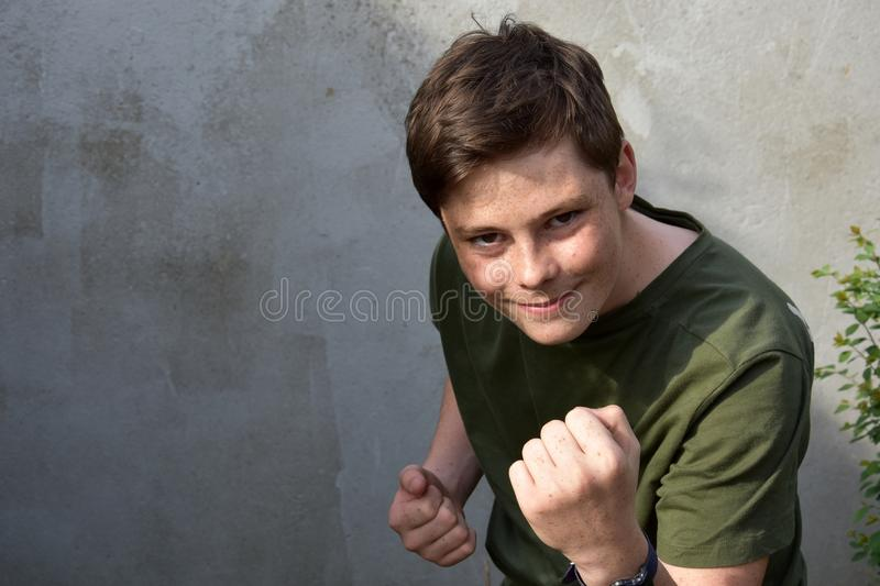 Boy with clenches fists, ready to fight back. Portrait of a confident boy, he clenches his fists, ready to fight back royalty free stock photography