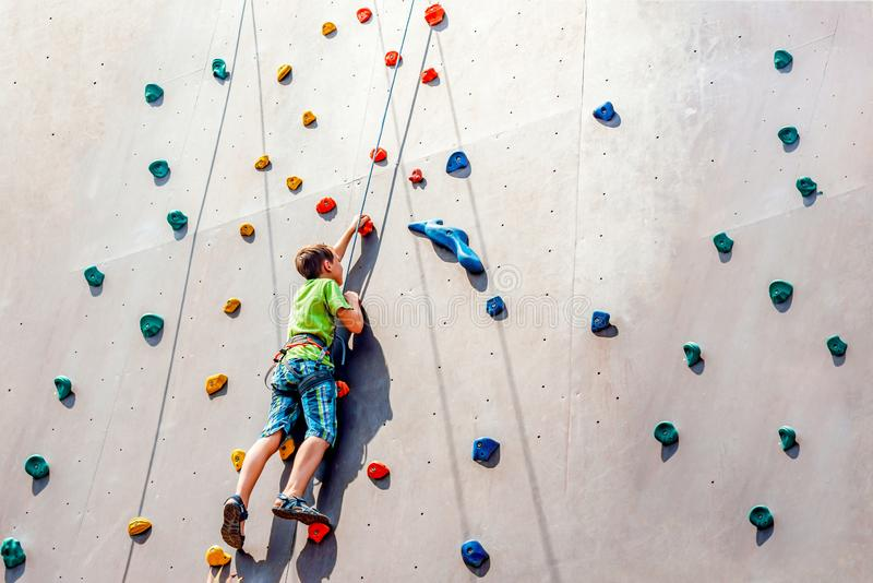The boy climber climbs on an artificial tower, overcoming obstacles on his way up royalty free stock image