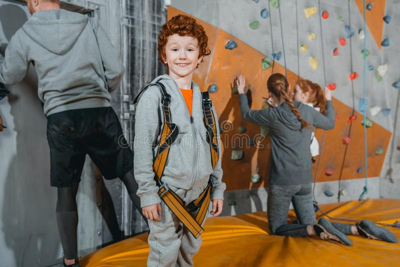 Half-length shot of a little red-headed boy. In a climbing harness standing at gym and looking at camera with climbing walls in the background stock images