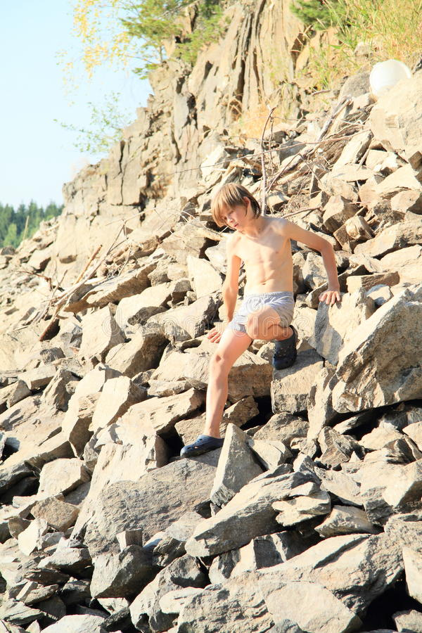 Boy climbing rock hill. Boy in grey shorts and crocks climbing steep rock hill on big stones royalty free stock photo