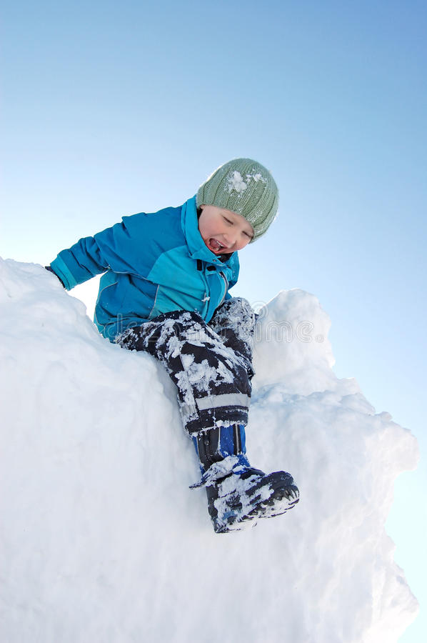 Download Boy climbing on snow pile stock image. Image of scared - 13669197