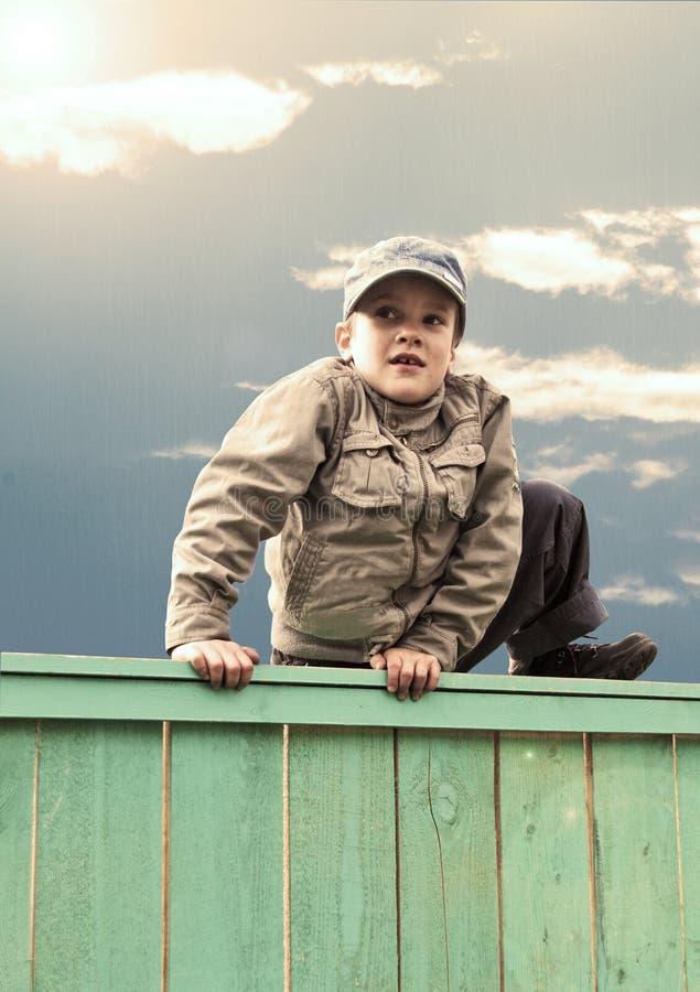 Free Boy Climbs Fence Royalty Free Stock Photos - 19670608