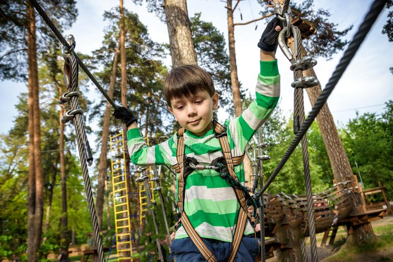 Boy climbs in a high wire park above the ground. ziplining. boy on the zip line. kid passes the rope obstacle course stock photo