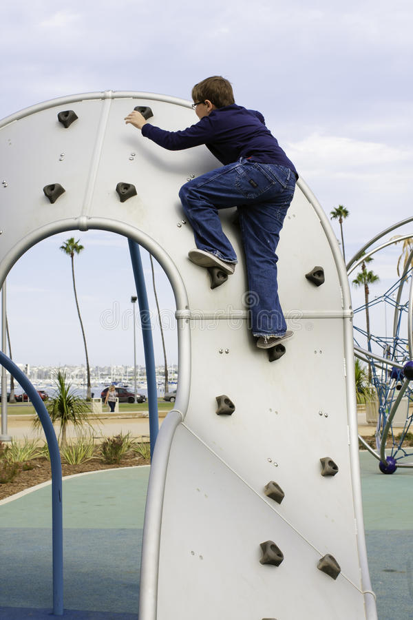 Boy climbs playground equipment royalty free stock photography