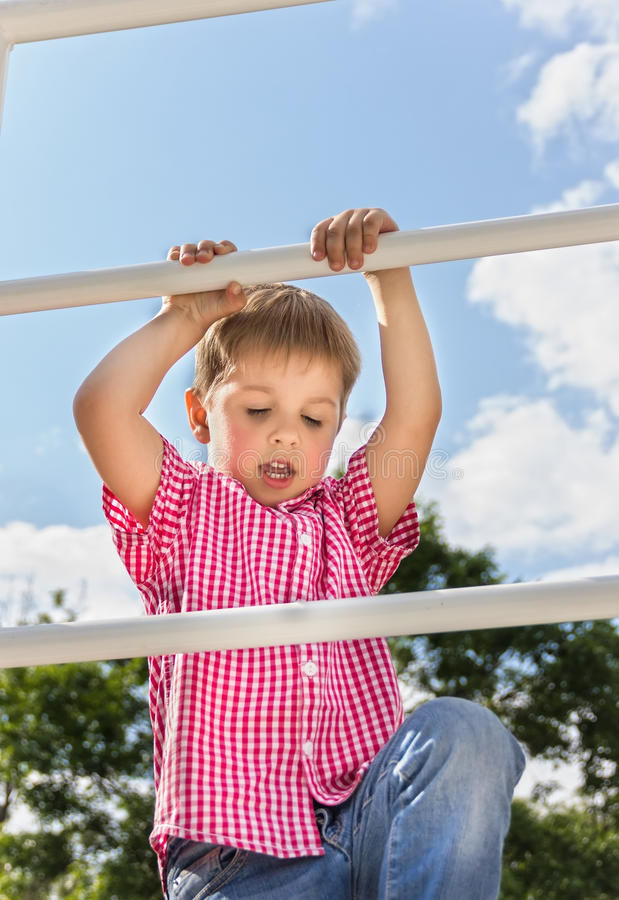 Boy climbs up on a ladder, a bottom view, in the open air against the blue of the sky royalty free stock images