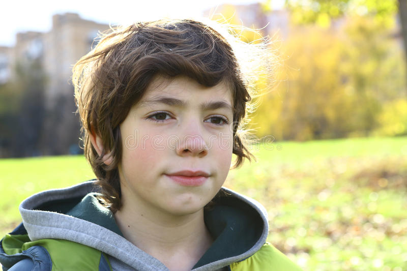 boy close up portrait in autumn city park stock photo