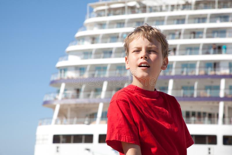 Boy closed eyes against background ship
