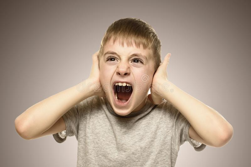 Boy closed his ears with his hands and shouts furiously. Naughty schoolboy. Fear.  stock photography