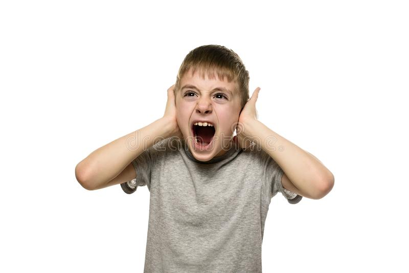 Boy closed his ears with his hands and shouts furiously. Naughty schoolboy. Isolate.  stock photo
