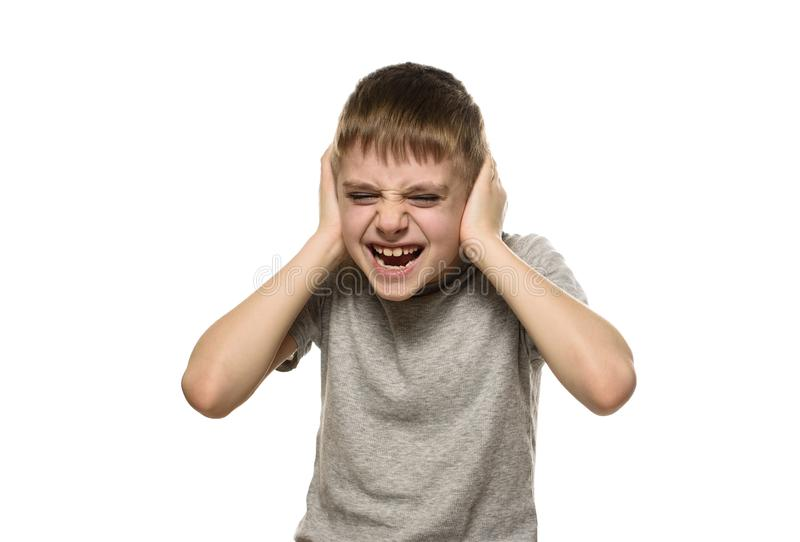 Boy closed his ears with his hands and shouts furiously. Naughty schoolboy. Isolate.  stock images